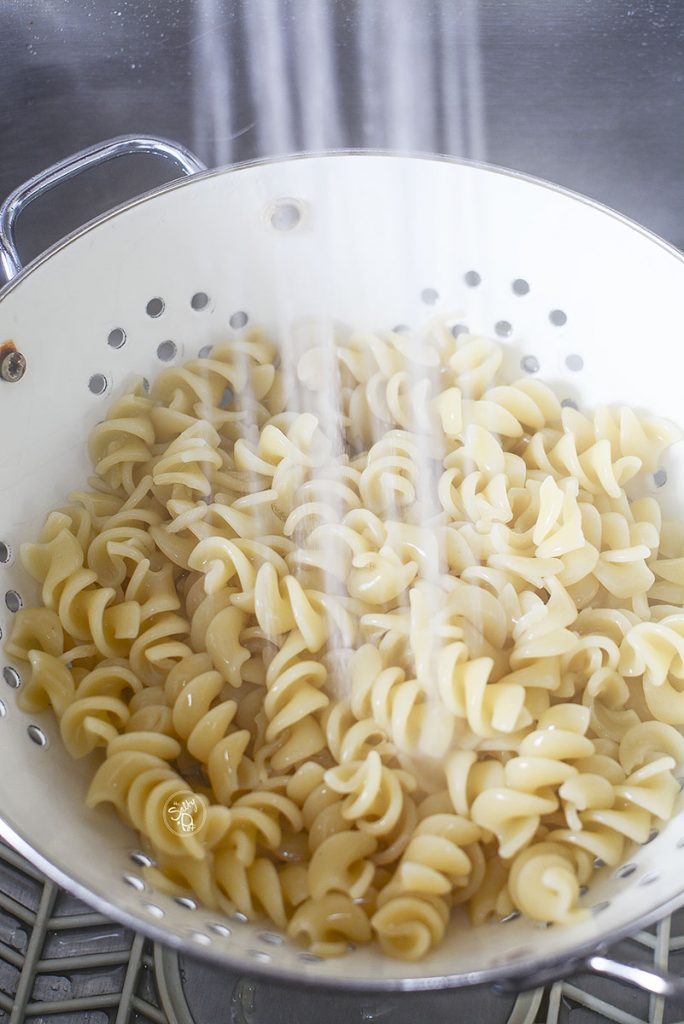 Cooked rotini pasta being rinsed under cold water in a colander to stop the cooking so it doesn't get mushy.
