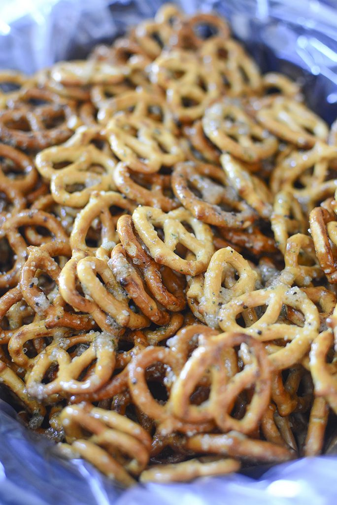 The seasoned pretzels are in the slow cooker, ready to be roasted.