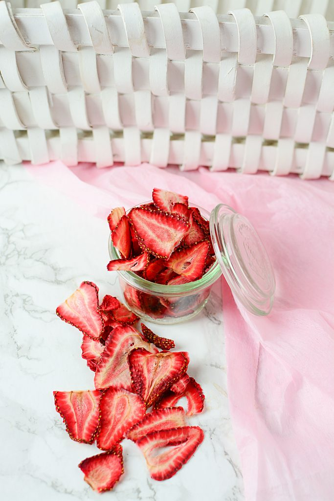 A pretty glass jar filled with overflowing dried strawberries resting close to a pink napkin. In front of the glass jar is the overflow of sliced, dried strawberries.