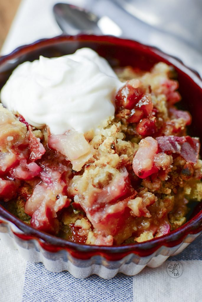 The closest view yet of this dessert is in this photo. Bits of the pear and rhubarb can be seen mixed in with the crumble topping. Whipped cream is dolloped over the top.