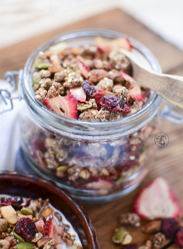A glass container holding the granola with a small wooden spoon on top.