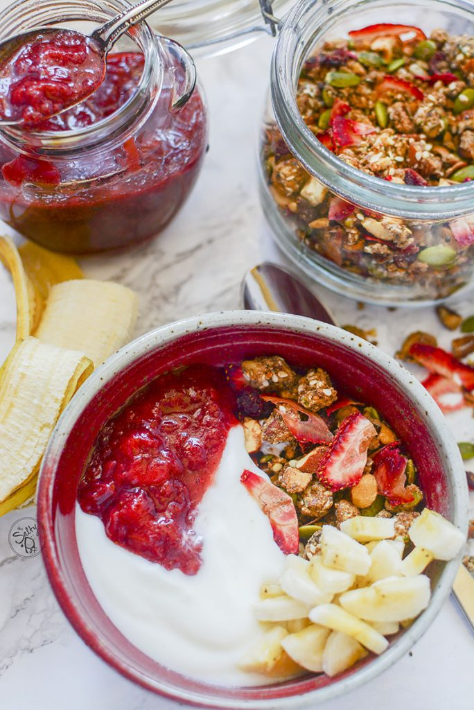 A red bowl at the bottom of the photo shows the granola bowl with strawberry compote, yogurt, and bananas on top. At the top of the photo is a jar of the strawberry jam on the left, and a jar of the granola on the right.