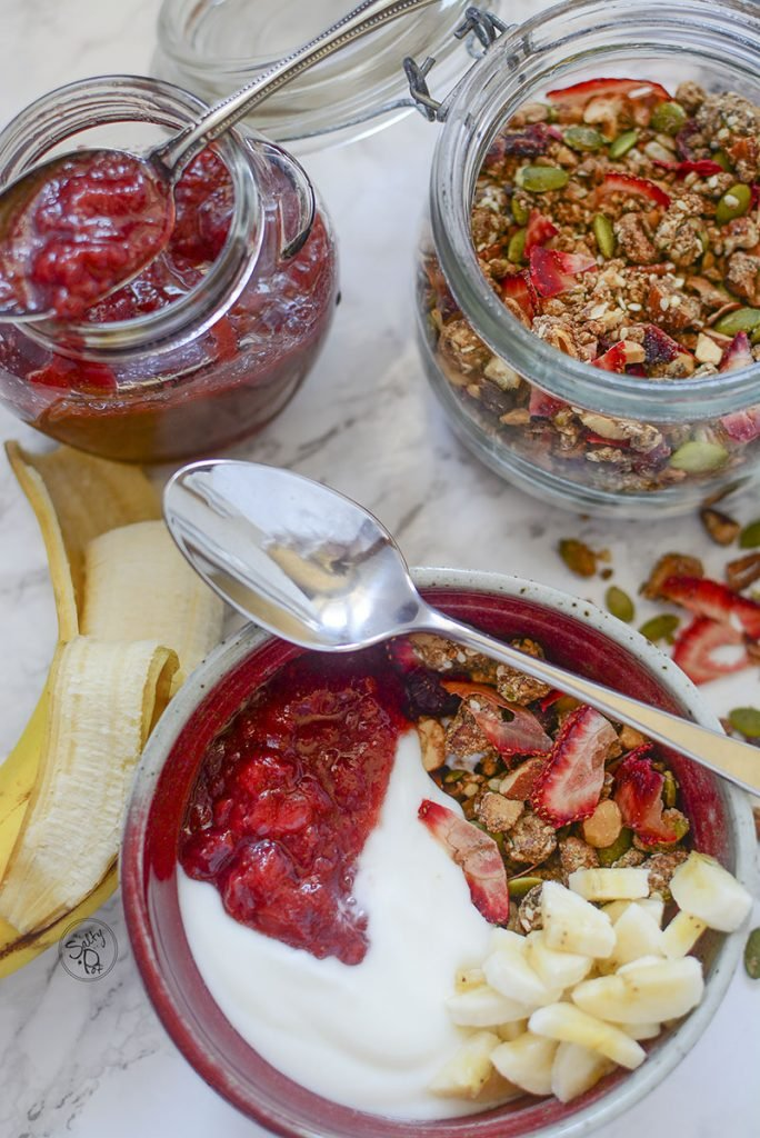 A top down photo of the breakfast table. Granola bowl on the bottom, a spoon resting on top of the bowl. The jam jar and granola jar sit to the top of the bowl with half a banana on the left.