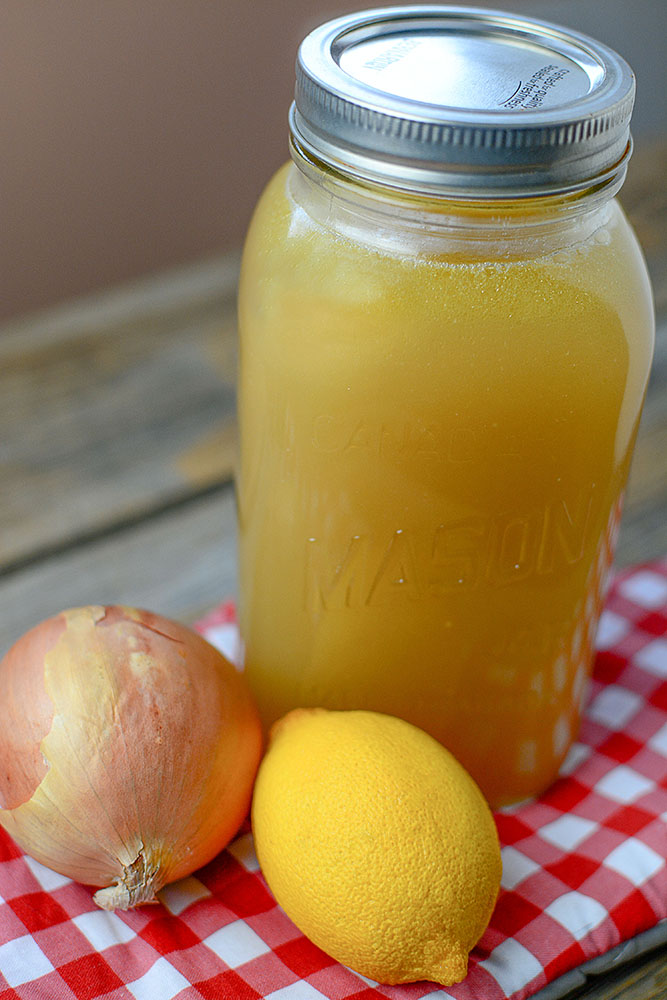 A large quart of homemade bone broth with a lemon and an onion sitting at the base of the jar.
