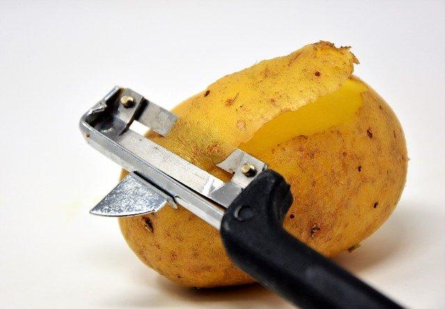 A potato peeler taking off the skin of the potato.