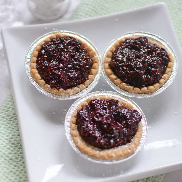 Three cherry tarts are sitting on a white plate with a shaker of icing sugar in the background.