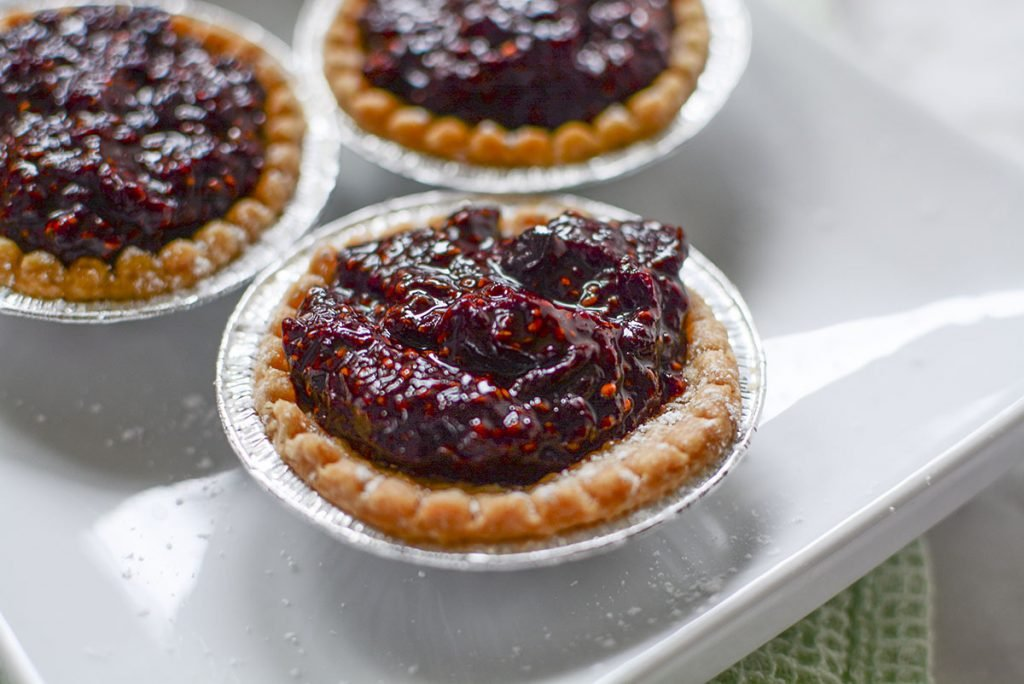 A closeup, 45 degree angle of the tarts on a white plate. The cherry filling is mounded in the center of the tart and looks delicious!