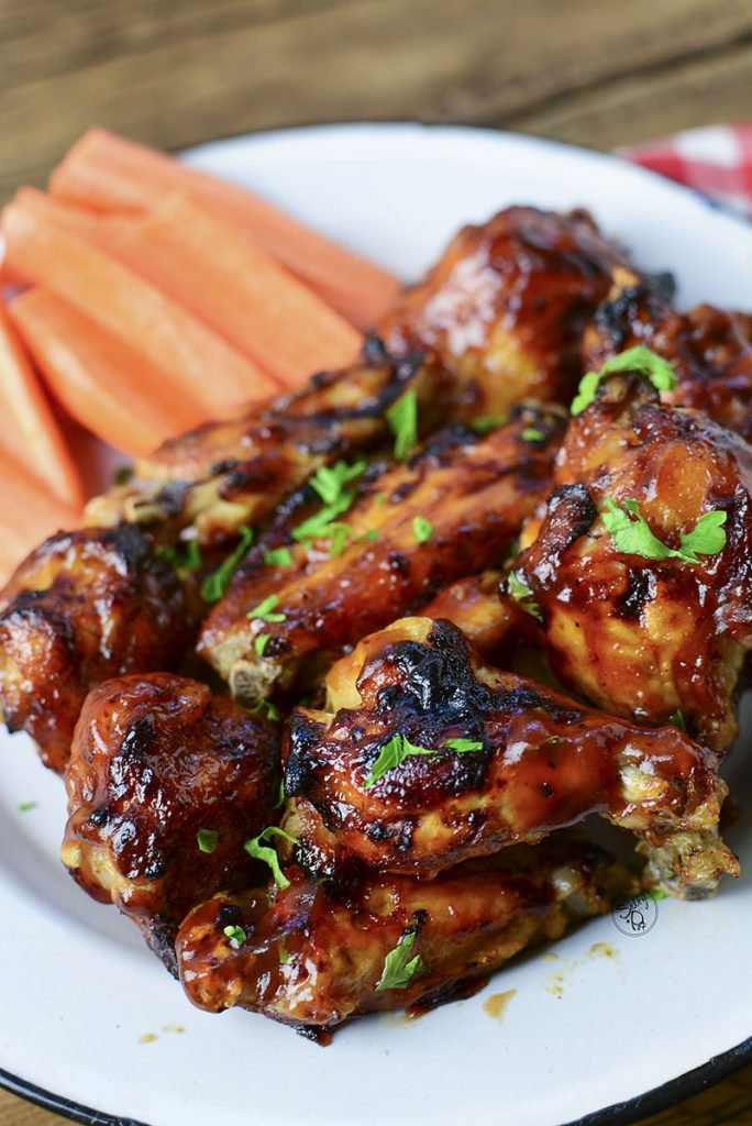 The pile of wings sitting on a white tin plate with carrot sticks in the background.