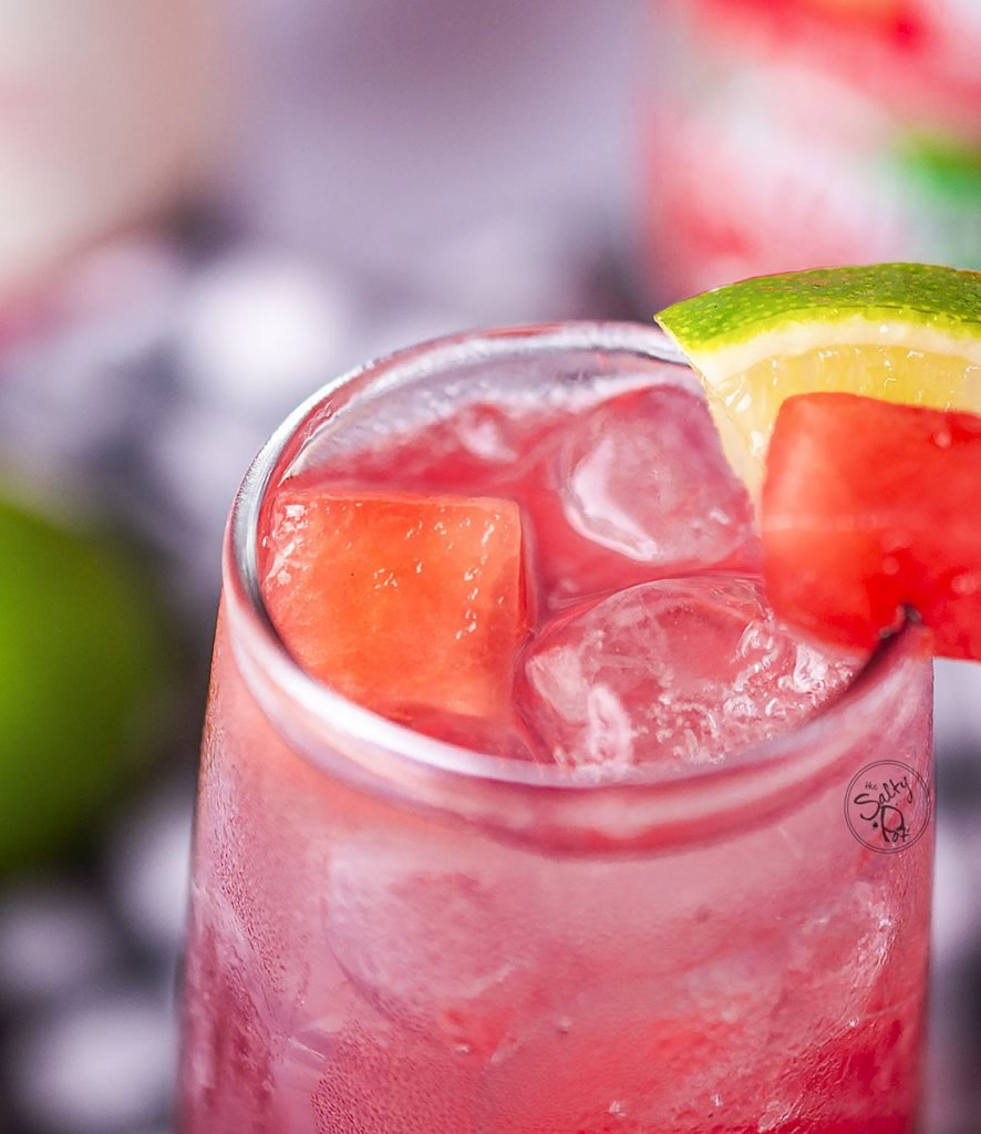 A close up photo of the drink that shows the top of the glass with the fruit on the rim.