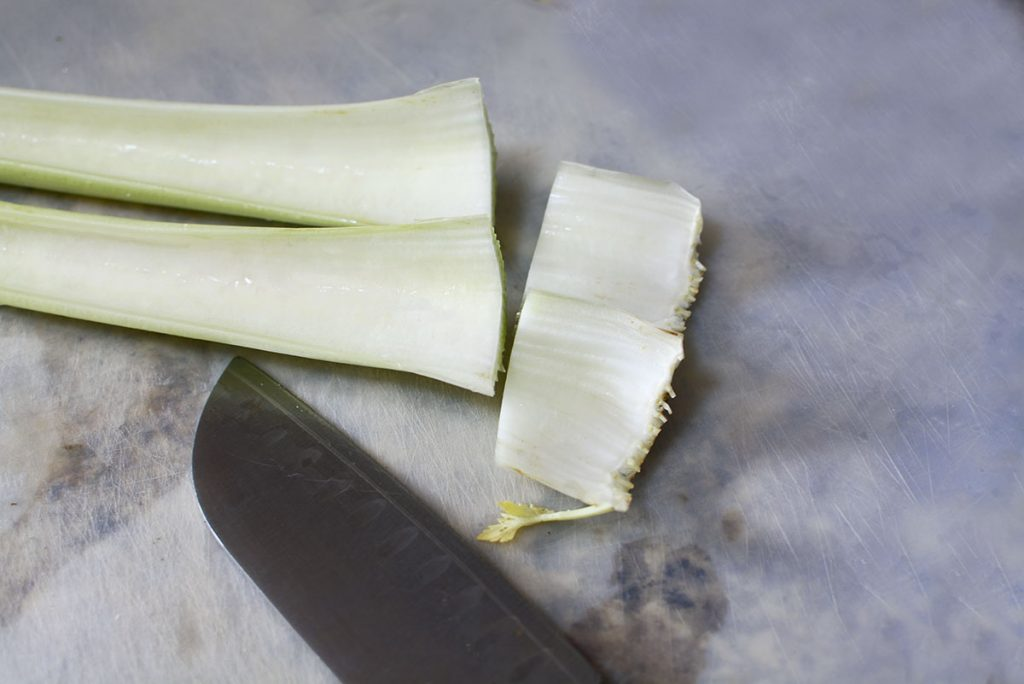 With a sharp knife, the ends are cut off the celery. They are very fibrous and not pleasant to eat.