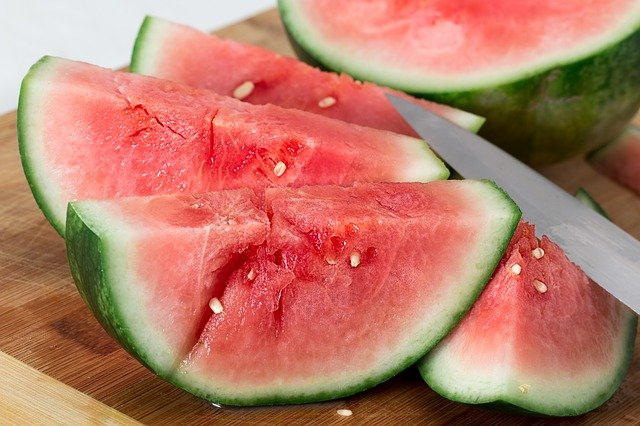 Watermelon slices on a cutting board with a knife cutting into a slice.