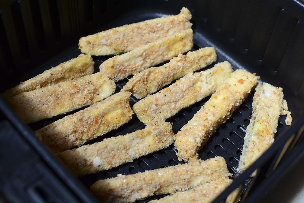 Zucchini fries in the fryer before the cheese has been put on.