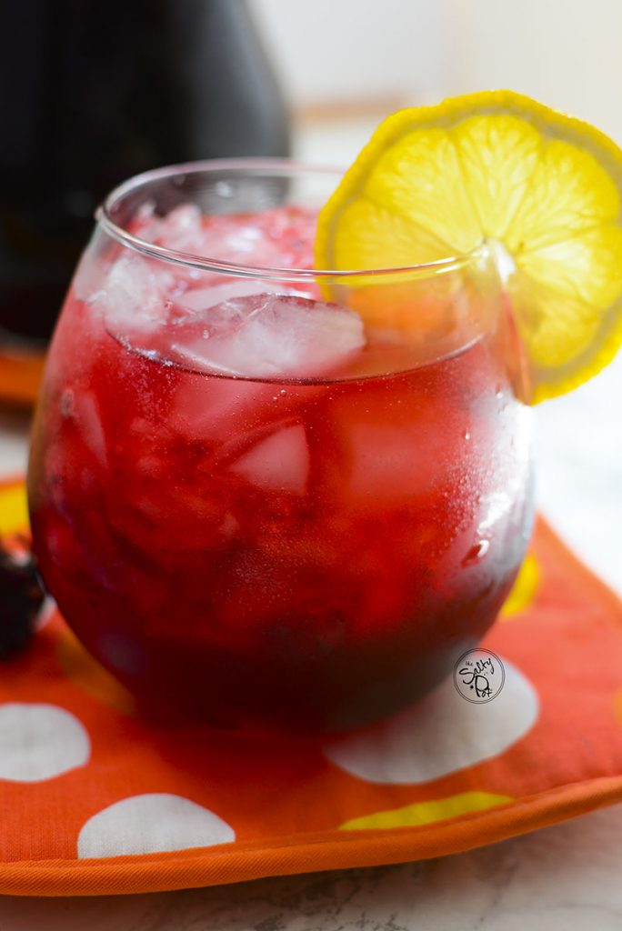 A glass of hibiscus iced tea with ice and lemon.