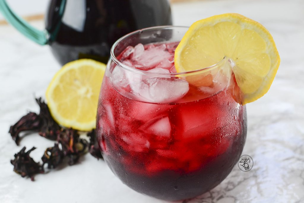 A 90 degree angle photo of the iced tea with lemon slices and dried hibiscus in the background.