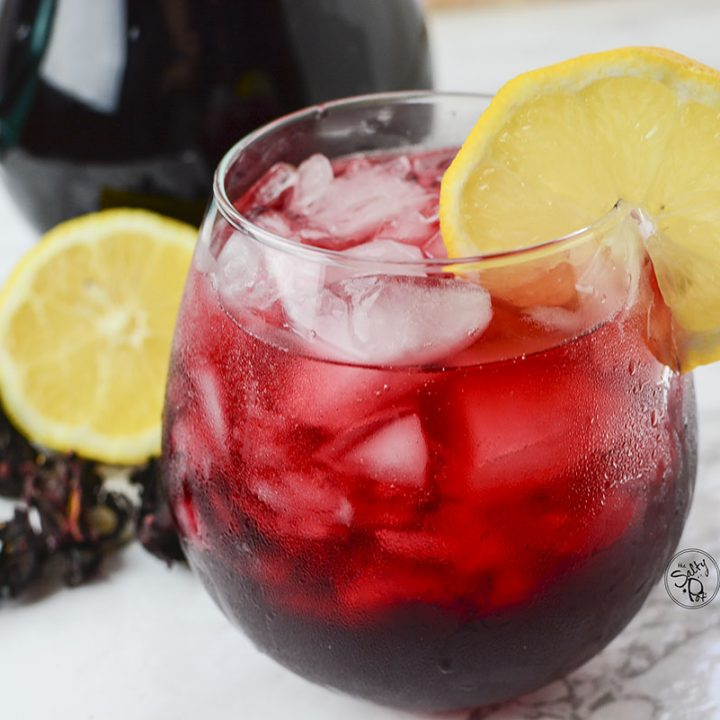 A side view of the iced tea with lemon and hibiscus in the background.