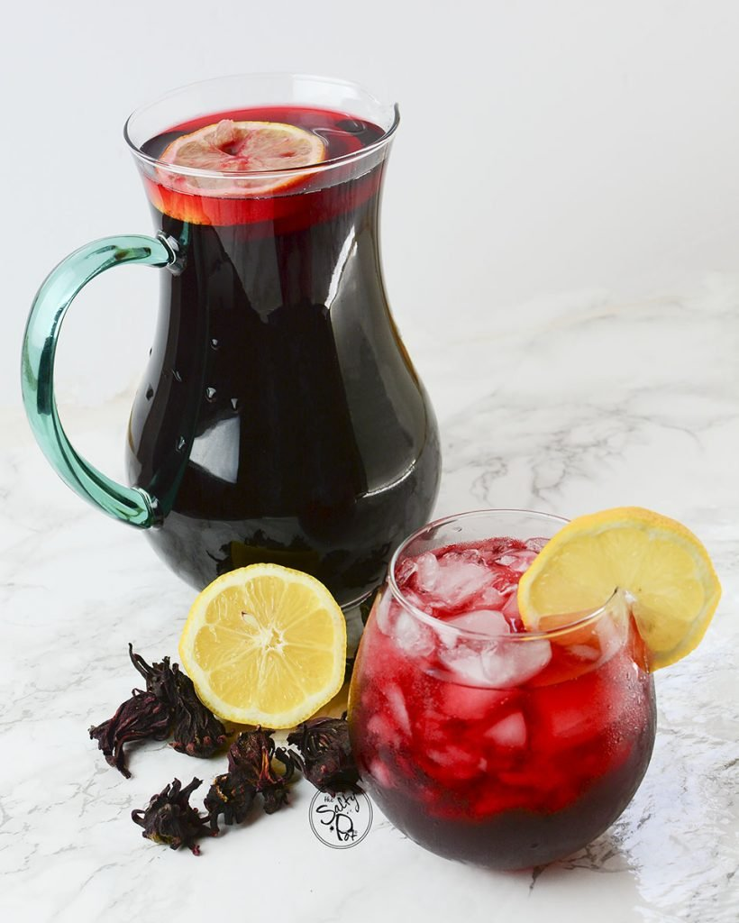 A pitcher and a glass with lemon slices and hibiscus tea.