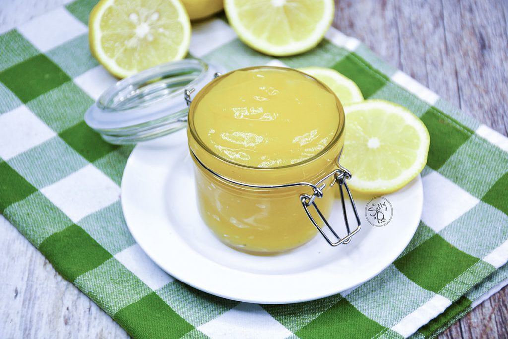 Lemon curd in a glass container with a glass flip lid. Lemons in the background.