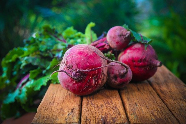 Beets on a wooden table with the greens still attached to the beets.