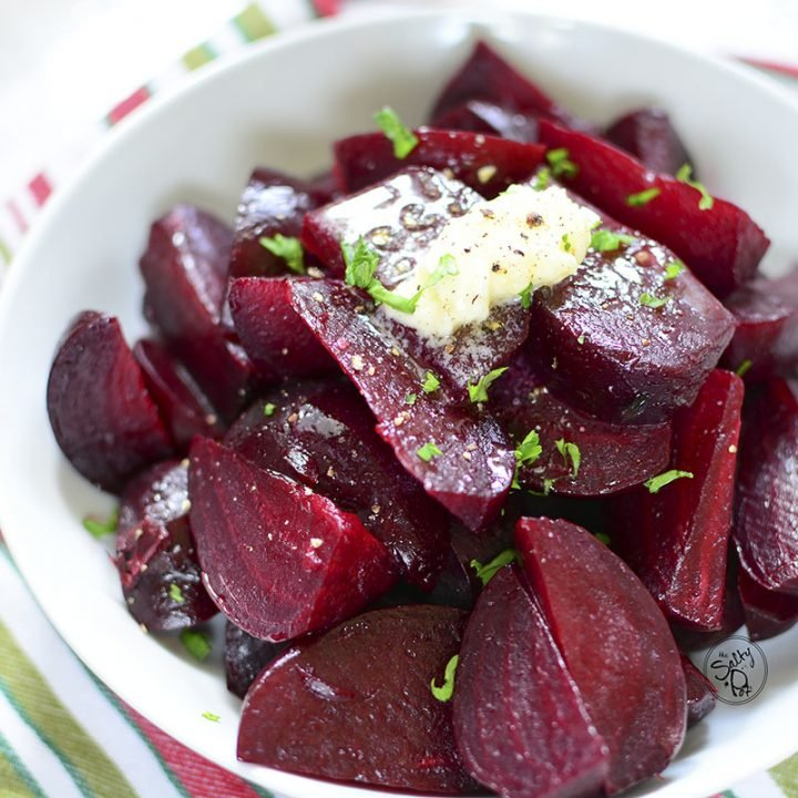 Beets in a white bowl with butter on top.