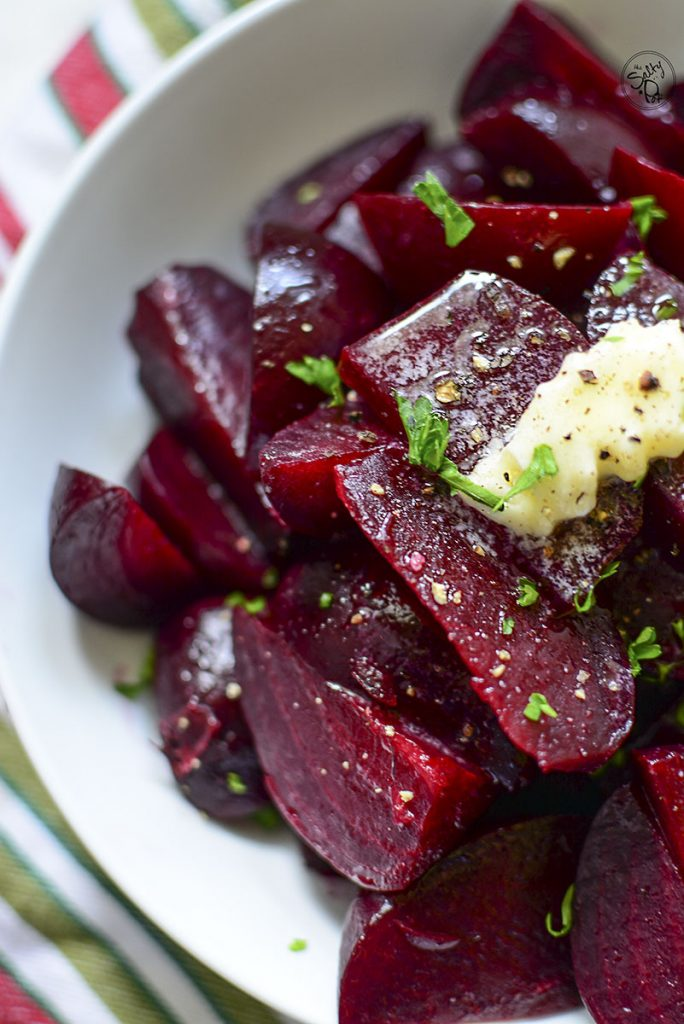 A photo showing half the bowl of beets with butter on top, closeup.