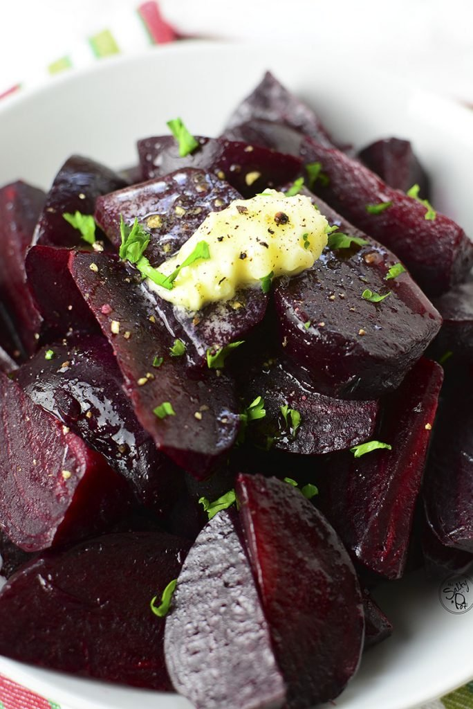 A closeup photo of cooked beets in a white bowl with a dollop of butter melting over the top.