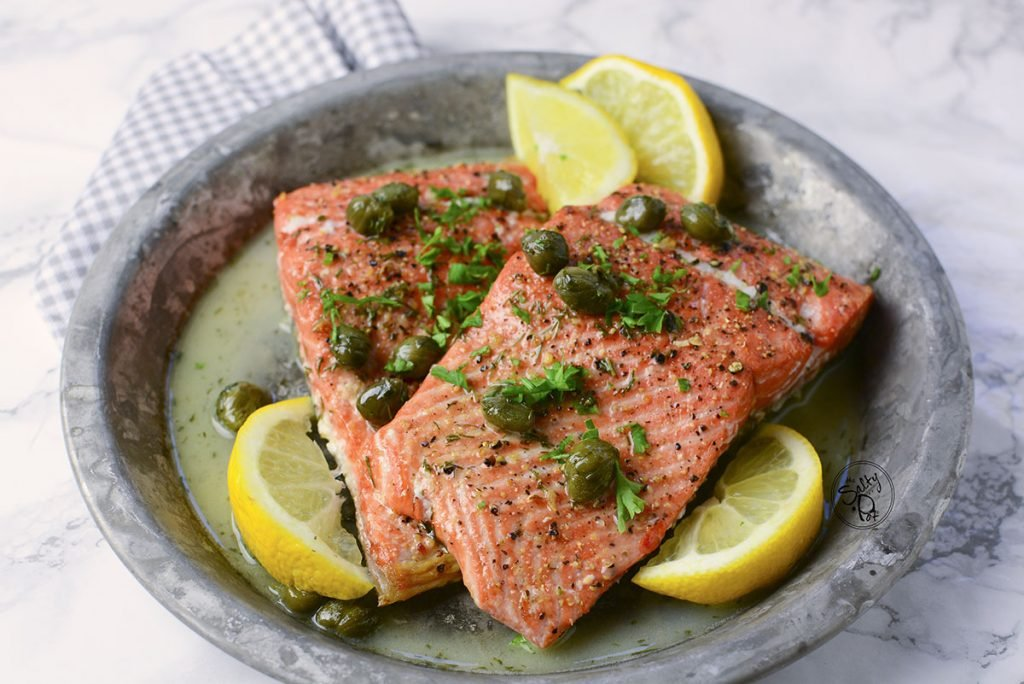 Air fryer salmon sitting on a plate with lemon wedges sitting around it, along with capers on top.