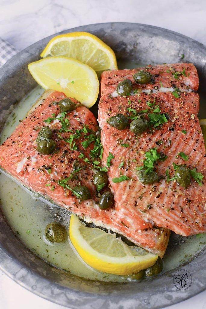 Two pieces of air fryer salmon sitting in a tin plate on a marble background.