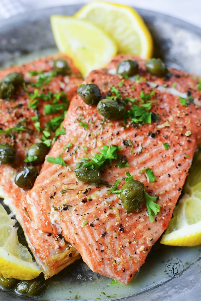 A close up photo of a cooked salmon filet with lemon wedges and green capers on top.