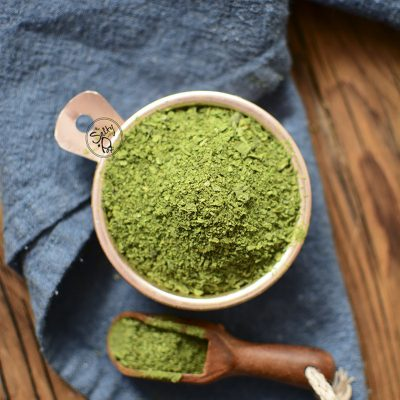 Spinach powder in a copper tin with a wooden spoon beside it on a blue napkin.