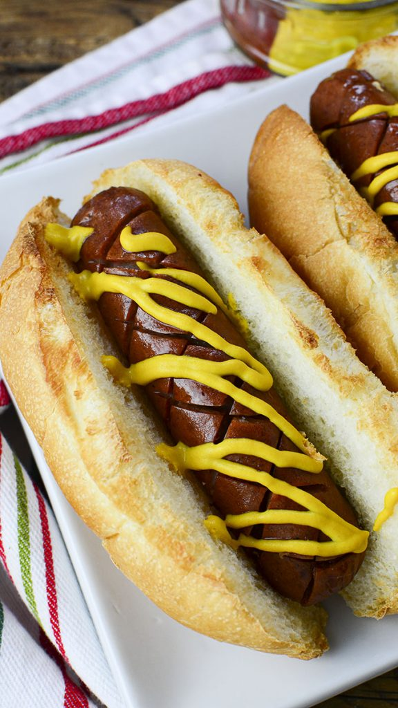 One hot dog cooked in an air fryer with a toasted bun on a white plate with mustard on top.