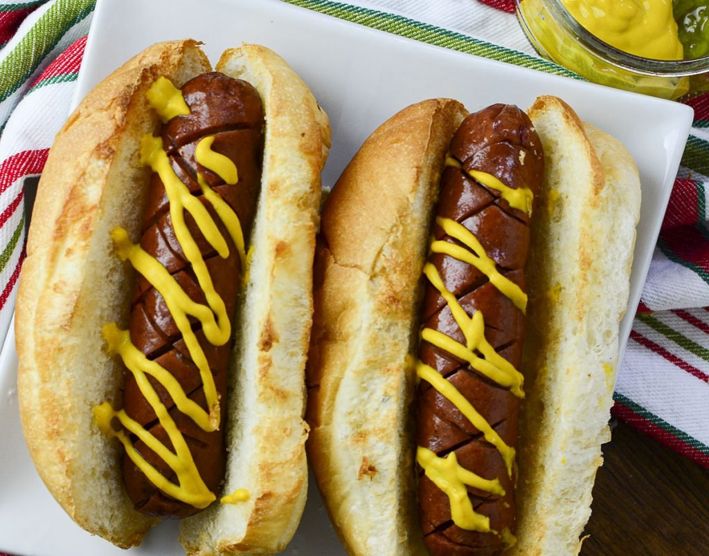 A top down photo of two air fried hot dogs in buns, sitting on a white plate with a colorful napkin in the background.