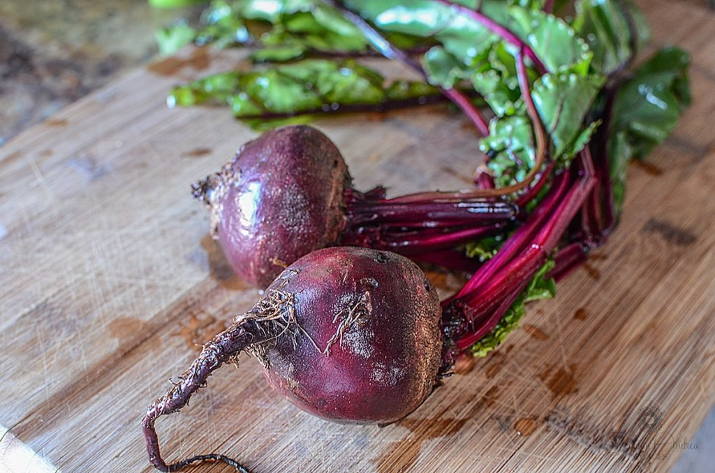 Two beets with greens still attached, sitting on a wooden cutting board.