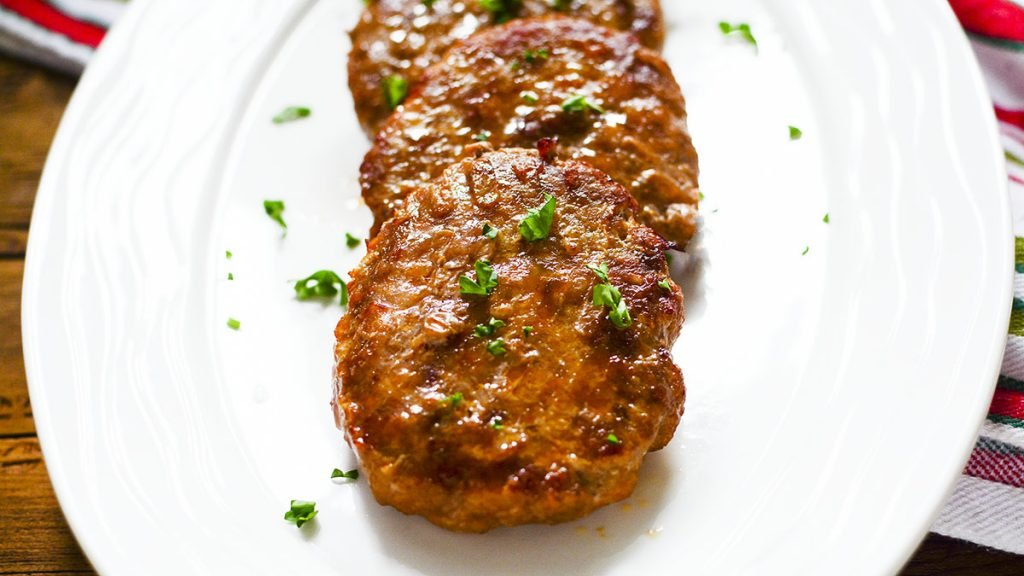 Three sausage patties lined up on a white plate with green parsley sprinkled over them.