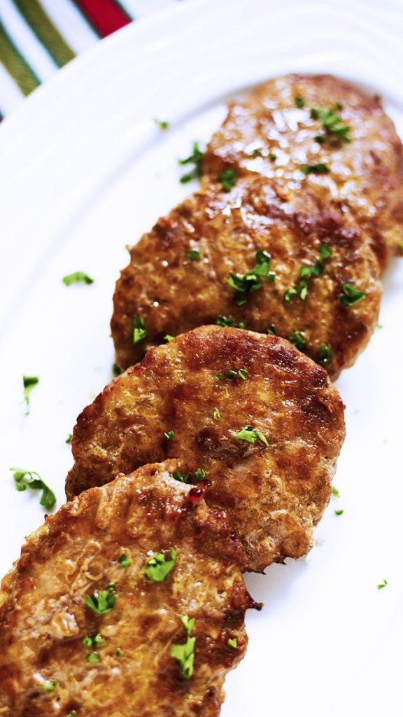 Four sausage patties laying in a domino fashion on a white plate.
