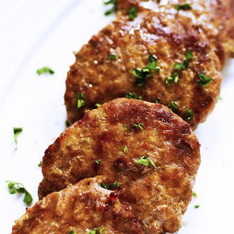 4 air fried sausage patties lined up on a white platter.