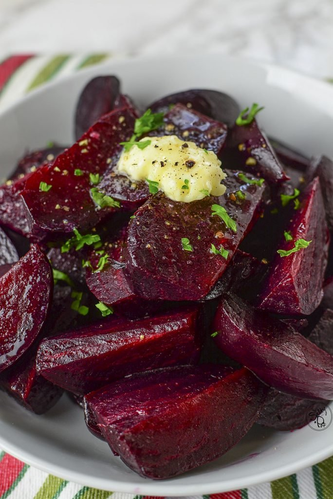 Ruby red pressure cooked beets sitting in a white bowl on a colorful napkin.