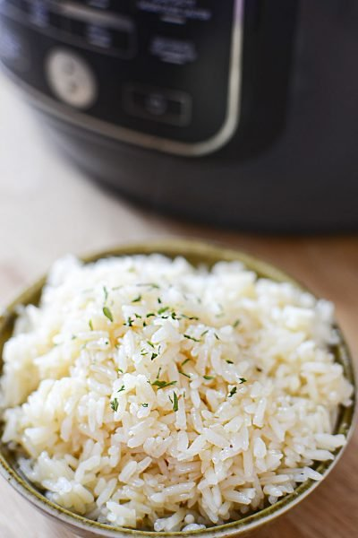Cooked white rice in a bowl with the ninja foodi in the background.
