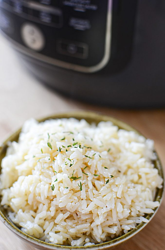 A close up photo of cooked rice in a green bowl with a sprinkle of parsley over top.