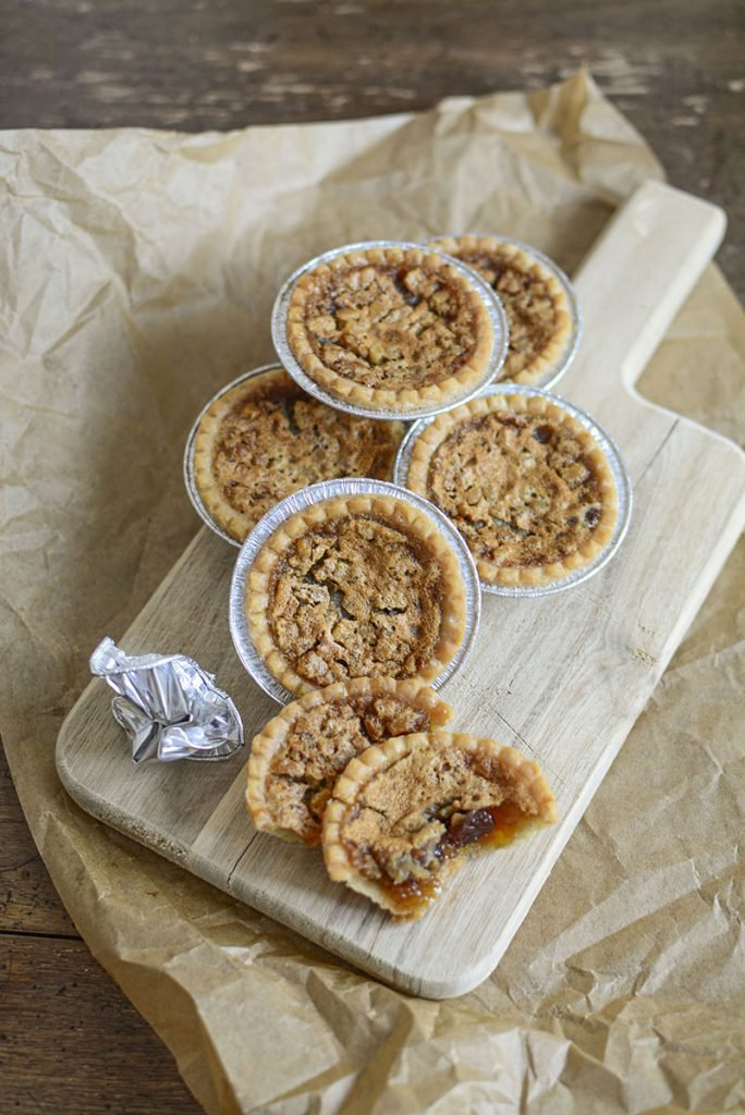 Butter tarts sitting on a board that has brown paper under it.